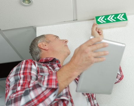 man-holding-tablet-checking-emergency-exit-sign-P3BU4AP